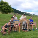 group of teenagers doing archery for a birthday