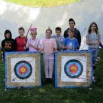group of kids with archery target