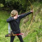 Woman shooting uphill with a longbow
