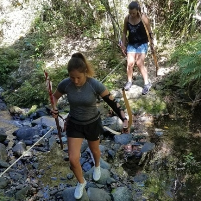 People with bow and arrow crossing a stream at Archery Park Nelson