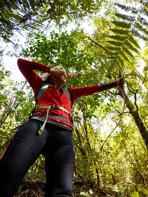 Woman focusing on intuitive traditional archery in a native forest in Nelson, New Zealand